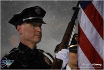 Honor Guard officer in serious pose with American Flag, while snow falls