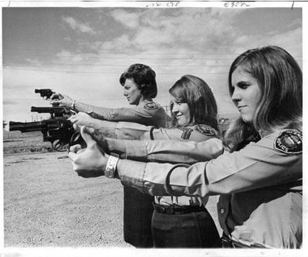 very old photo of three dispatchers shooting revolvers